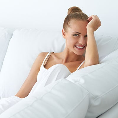 Happy woman sitting on couch Face Skin Care. Facial Hydro Microdermabrasion Peeling Treatment