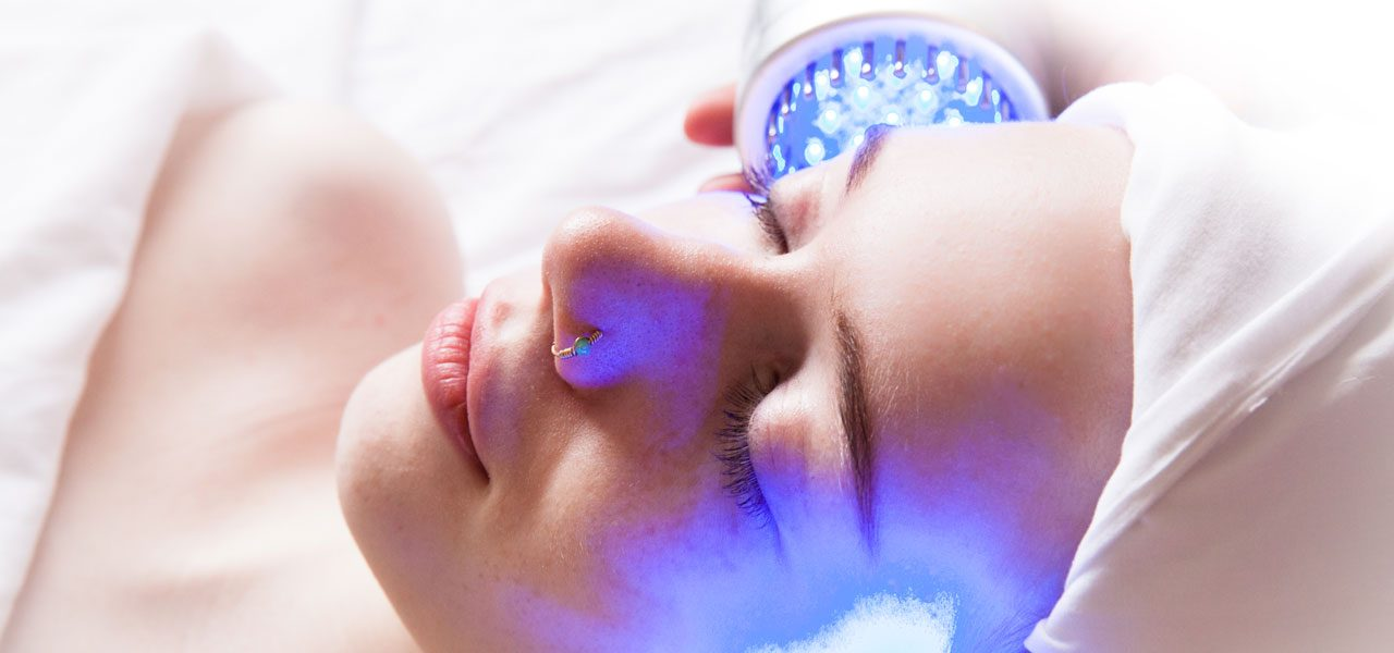 Young woman gets violet light LED microcurrent facial