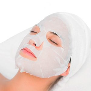 Relaxing Sheet mask facial on young woman Face Skin Care. Facial Hydro Microdermabrasion Peeling Treatment